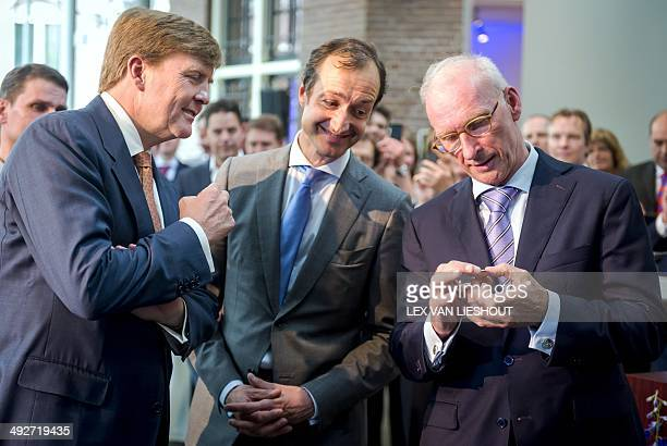 Dutch King WillemAlexander Secretary of Finance Eric Wiebes and coin master Maarten Brouwer look at a coin during the last minting of a coin with the...
