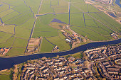 Aerial view of a village separated from green fields by a canal, The Netherlands