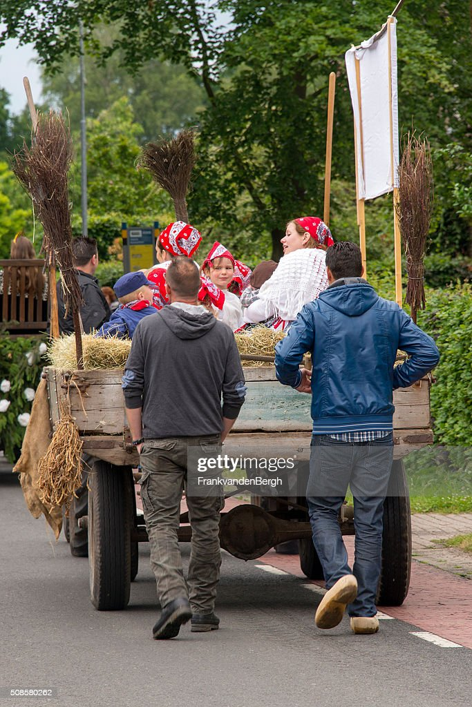 Dutch men on clogs behind a cart with dressedup people : Stockfoto