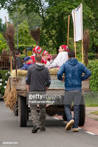 Dutch men on clogs behind a cart with dressedup people : Stock Photo