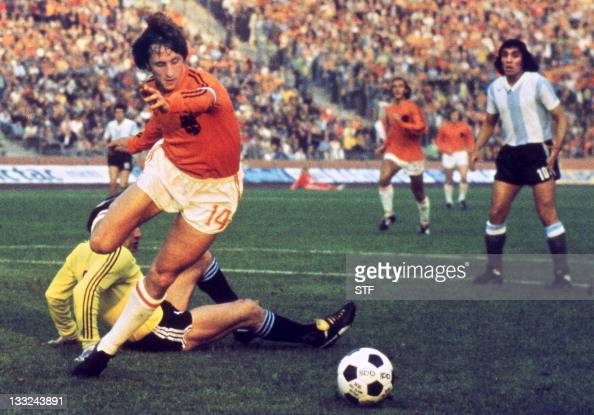 Dutch midfielder Johann Cruyff dribbles past Argentinian goalkeeper Daniel Carnevali on his way to scoring a goal during the World Cup quarterfinal...