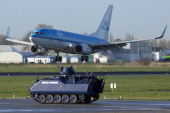 A Dutch military police armored vehicle guards the runway prior to the arrival of the US President at Schiphol Amsterdam Airport the Netherlands on...