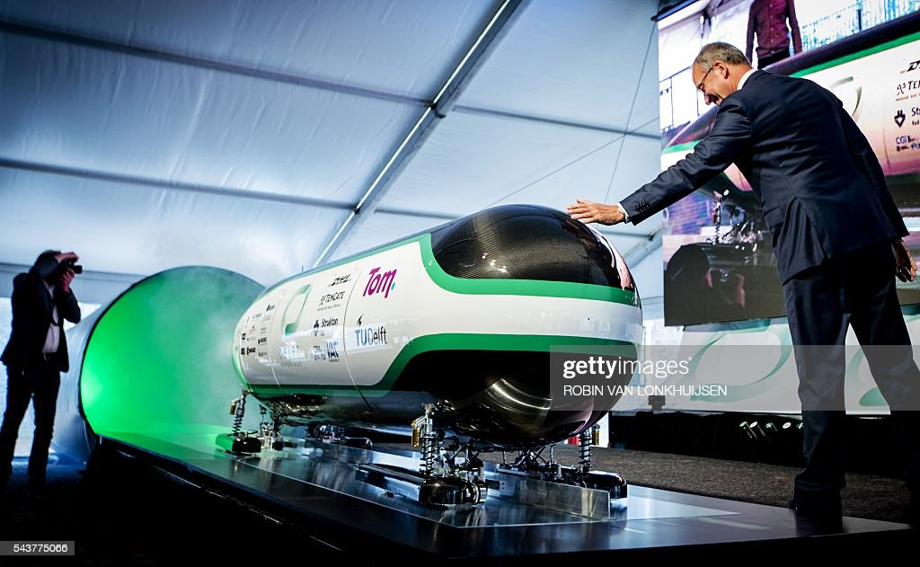 Dutch Minister for economic affairs Henk Kamp (R) touches the prototype during the unveiling of the Hyper Loop capsule from the Delft University of Technology in Delft on June 30, 2016. Students will compete late this summer in the Hyperloop Pod Competition in California with this capsule. / AFP / ANP / Robin van Lonkhuijsen / Netherlands OUT