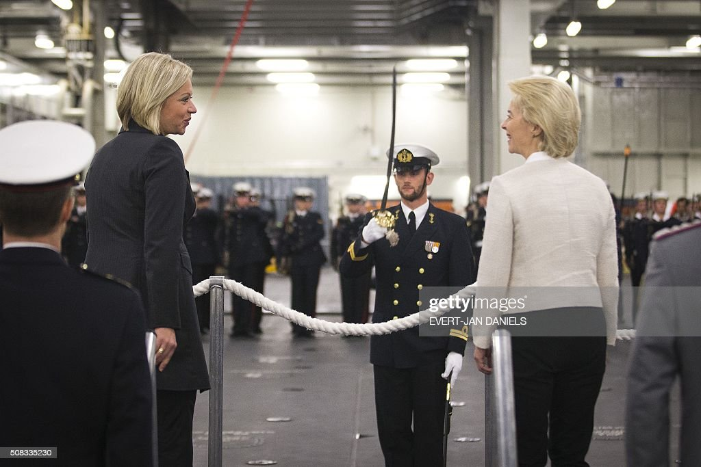 Dutch Minister of Defence Jeanine Hennis-Plasschaert (L) and German Minister of Defence Ursula von der Leyen stand together prior to the signing of a statement on closer cooperation in the field of naval activity on board the Dutch ship, the Joint Logistic Support Ship (JSS) Zr. Ms. Karel Doorman, in Amsterdam, on February 4, 2016. / AFP / ANP / Evert-Jan Daniels / Netherlands OUT