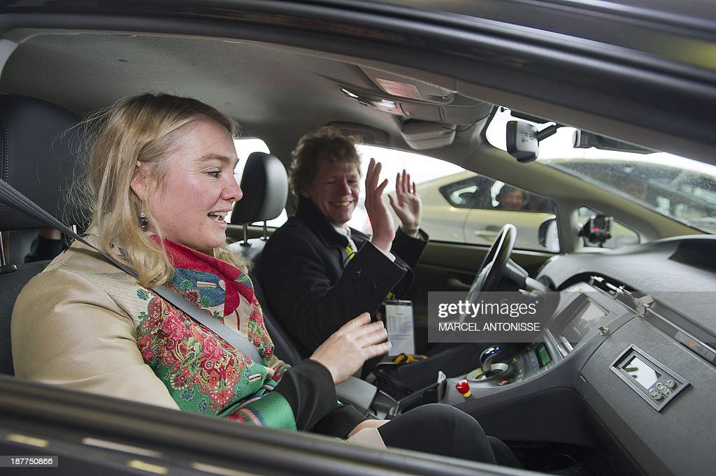 Dutch Minister of Infrastructure and Environment Melanie Schultz van Haegen (L) sits in a self-driving car on November 12, 2013. The self-driving car was tested for the first time on a public road. The self driving car is a Toyota, Davi (Dutch Automated Vehicle Initiative), designed by innovation company TNO, Technic University Delft and the National Office for road traffic (Rijksdienst voor wegverkeer). The car has cameras, a radar and other sensors to follow traffic movements. For now the car's production is in a test phase and it is not known when the car might be released for sale to the general public. AFP PHOTO / ANP / MARCEL ANTONISSE
