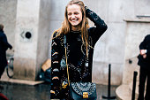 Dutch model Ine Neefs wears a black embroidered sweater dress and carries a small blue green Furla purse after the Redemption show at Palais de Tokyo...