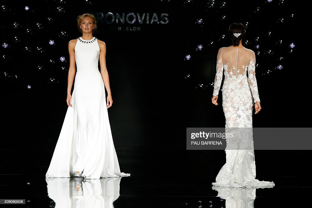 Dutch model Romee Strijd (L) and Russian model Irina Shayk present creations of the Pronovias 2016 collection during a press preview on the last day of the Barcelona Bridal Week in Barcelona, on April 29, 2016. / AFP / PAU