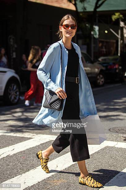 Dutch model Vera Van Erp wears red sunglasses a light blue shirt black belted jumpsuit a black YSL purse and yellow animal print shoes after the...