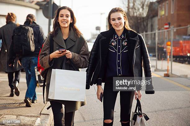 Dutch models Nirvana Naves wearing a green coat and Vera Van Erp wearing a black shearling bomber jacket with a blue floral button up top exit the...
