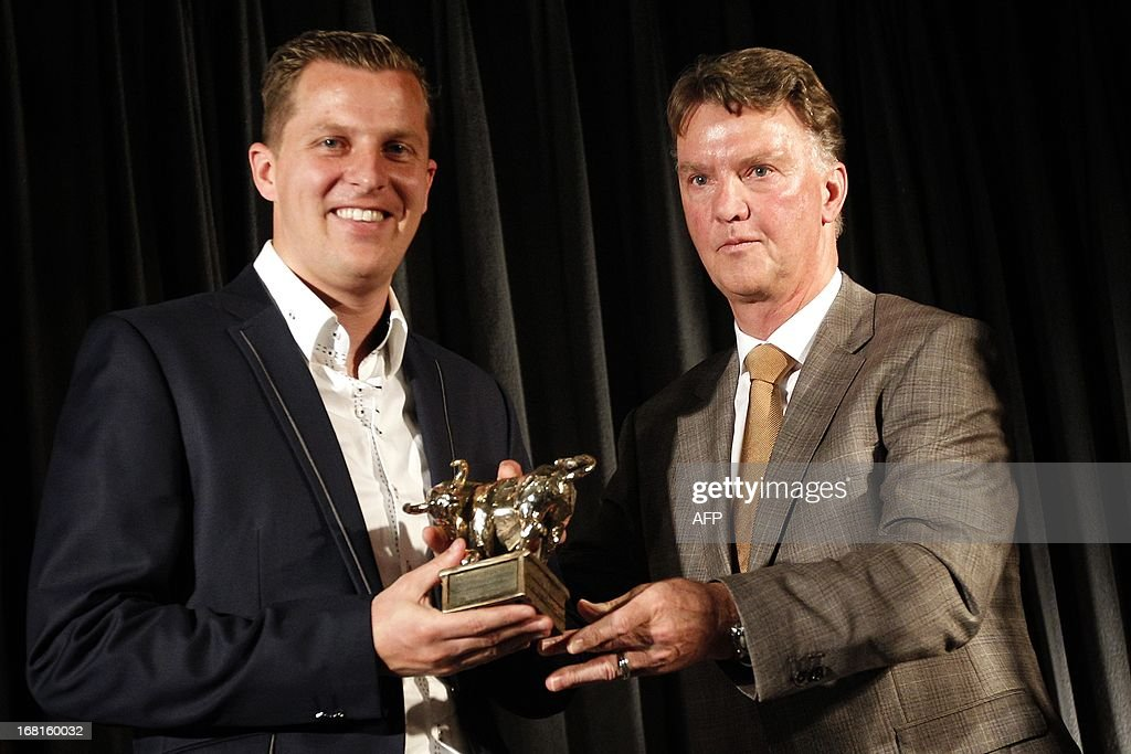 Dutch national football team head coach Louis van Gaal (R) hands the Gouden Stier (golden bull) award for the best player of the Jupiler League to Jack Tuyp (L) of FC Volendamduring, during the fifth edition of the ceremony of the Gouden Stier awards in Rhenen, the Netherlands, on May 6 2013. The Gouden Stier awards are given annually to the best talent, the best trainer, the top scorer and a captain of the 2012/2013 Dutch football Jupiler League.
