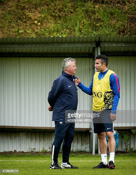 Dutch National football team player Robin van Persie speaks with head coach Guus Hiddink during a training session in Hoenderloo on June 2 three days...