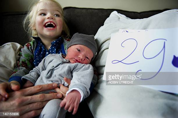 Dutch newborn Guus is held by an unidentified girl on February 29 2012 aferr being born earlier in the day in Amsterdam The baby was born in a leap...