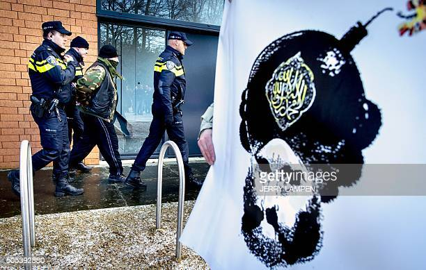 Dutch police officer detain a man next to a banner depicting a Mohammed cartoon during a rally of members of the German antiIslamic political...