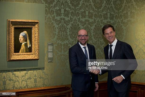 Dutch Prime Minister Mark Rutte and his Belgian counterpart Charles Michel shake hands as they pose next to Vermeer's 'Girl with a Pearl Earring' at...