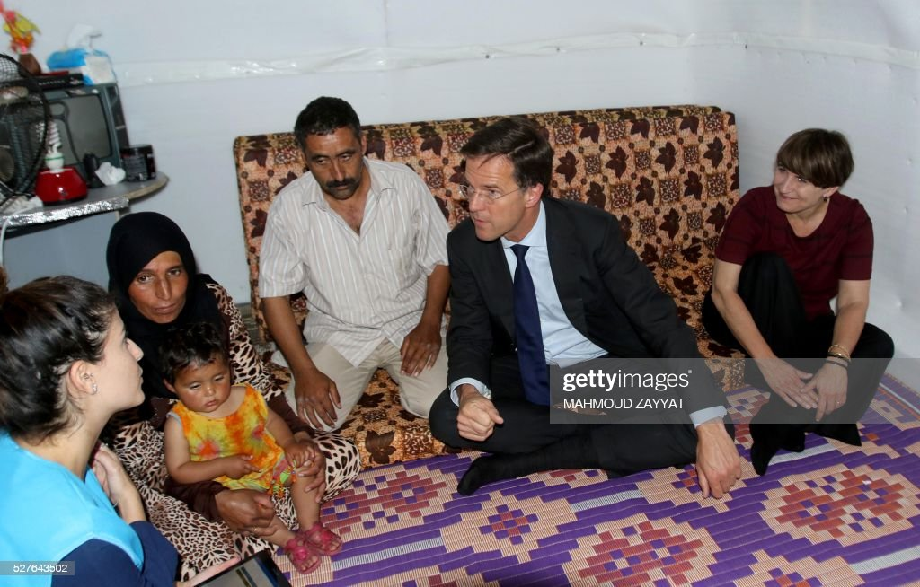 Dutch Prime Minister Mark Rutte (2-R) and Lilian Blomn (R), Minister of Foreign Trade Affairs and Cooperation and Development, speak to a Syrian family during a visit to a Syrian refugee camp, in the southern Lebanese town of Zahrani on May 3, 2016. / AFP / MAHMOUD