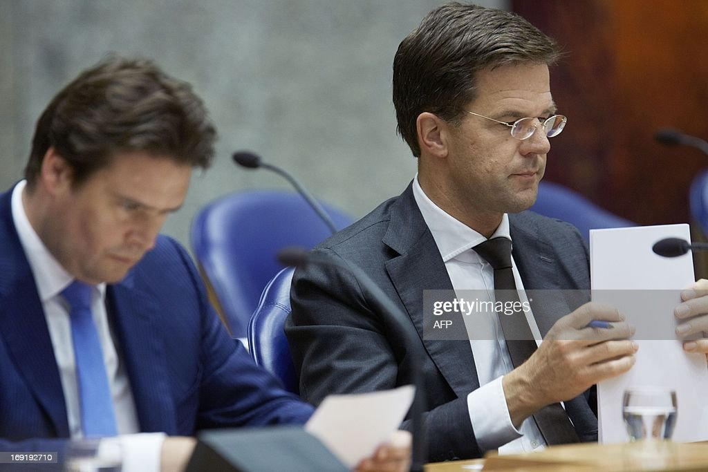 Dutch Prime Minister Mark Rutte (R) and State Secretary of Finance Frans Weekers attend a debate in the Dutch House of Representatives in The Hague, on May 21, 2013.