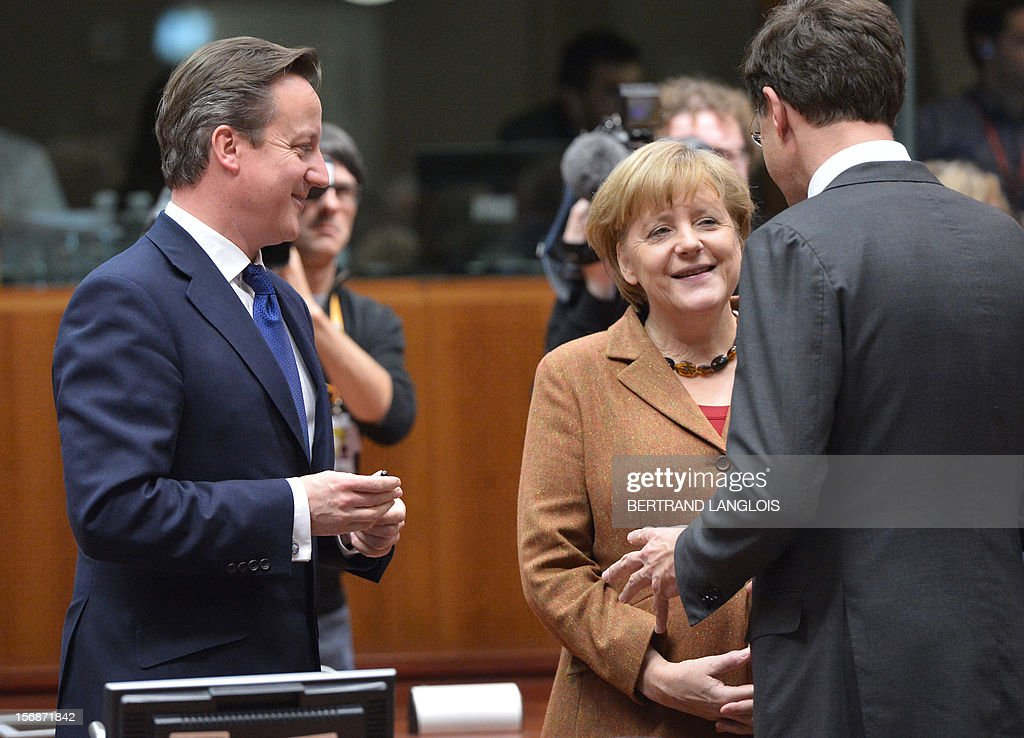 Dutch Prime Minister Mark Rutte (R) chats with German Chancellor Angela Merkel as British Prime Minister David Cameron (L) looks on at the EU Headquarters on November 22, 2012 in Brussels, during a two-day European Union leaders summit called to agree a hotly-contested trillion-euro budget through 2020. European Union officials were scrambling to find an all but impossible compromise on the 2014-2020 budget that could successfully move richer nations looking for cutbacks closer to poorer ones who look to Brussels to prop up hard-hit industries and regions.