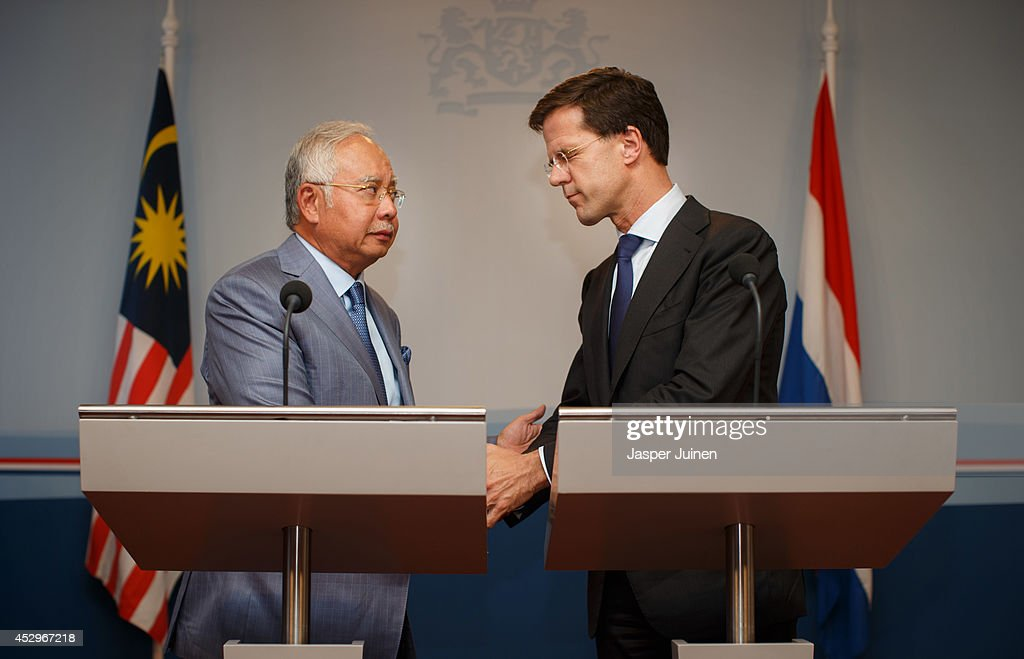 Dutch Prime minister <a gi-track='captionPersonalityLinkClicked' href=/galleries/search?phrase=Mark+Rutte&family=editorial&specificpeople=4509362 ng-click='$event.stopPropagation()'>Mark Rutte</a> (R) closes his eyes as he holds hands with Malaysian Prime Minister Najib Razak after they made a statement on July 31, 2014 in The Hague, Netherlands. Razak is in the Netherlands on a two-day working visit for talks about the Malaysia Airlines Flight MH17 crash in Ukraine.