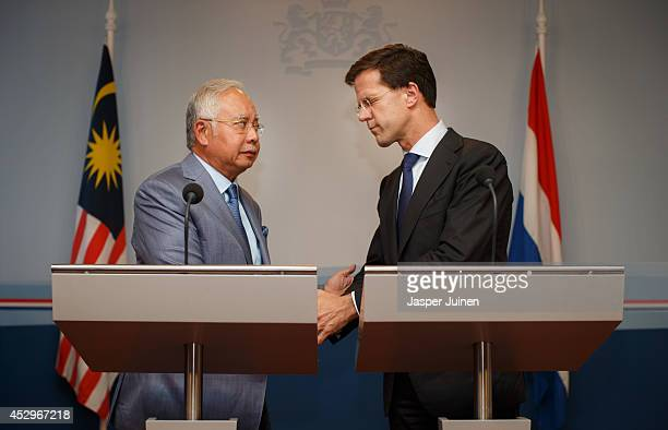 Dutch Prime minister Mark Rutte closes his eyes as he holds hands with Malaysian Prime Minister Najib Razak after they made a statement on July 31...