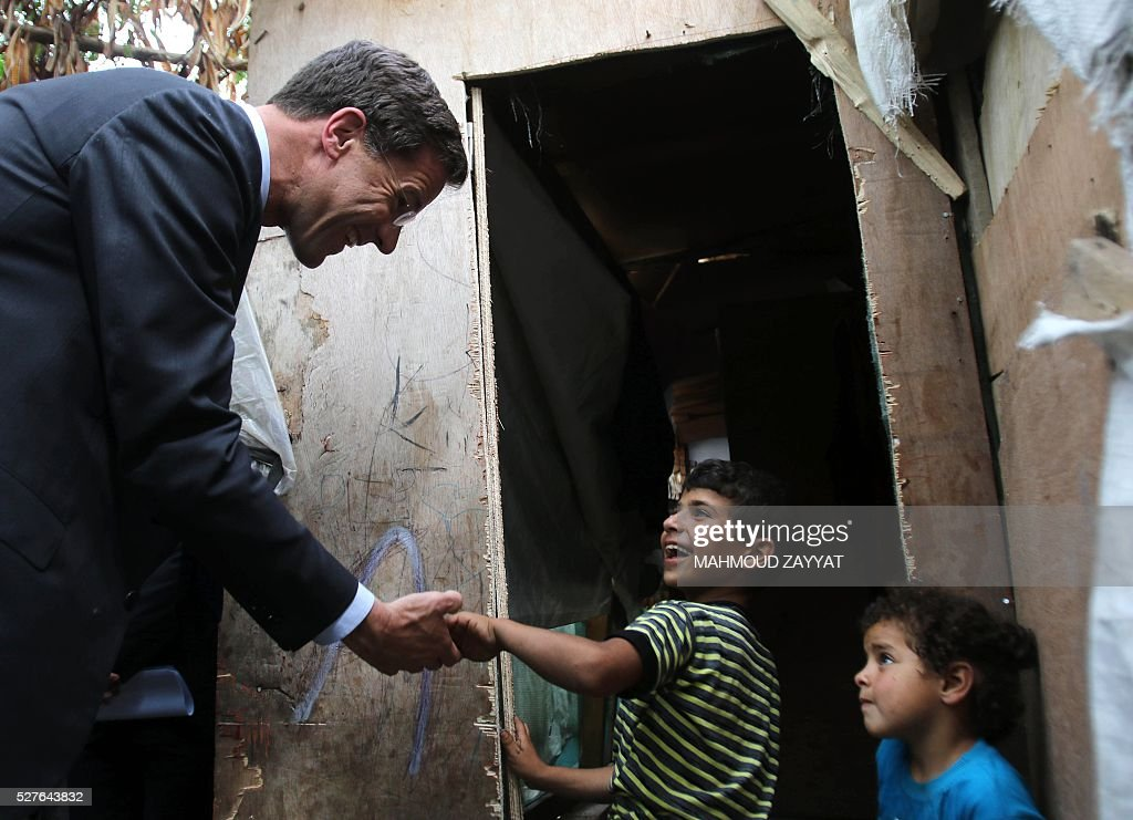 Dutch Prime Minister Mark Rutte (L) greets children during a visit to a Syrian refugee camp, in the southern Lebanese town of Zahrani on May 3, 2016. / AFP / MAHMOUD