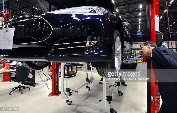 Dutch Prime Minister Mark Rutte looks at a car as he visits the Tesla car factory in Tilburg The Netherlands on March 11 2014 Tesla Motors today...