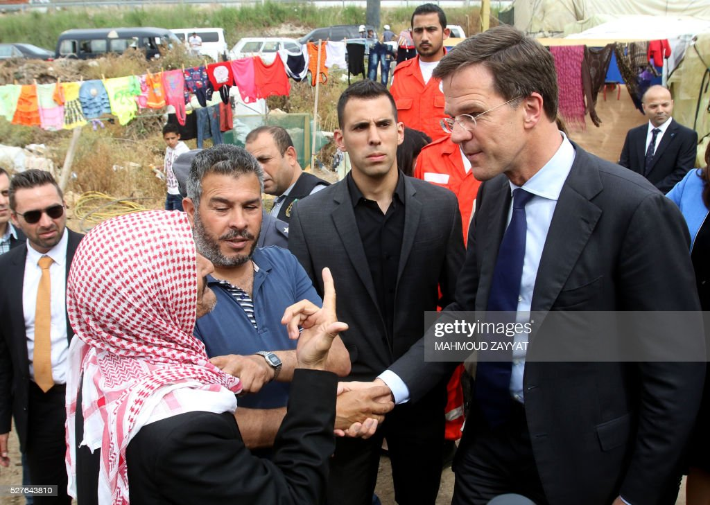 Dutch Prime Minister Mark Rutte (R) shakes hands with a man during a visit to a Syrian refugee camp, in the southern Lebanese town of Zahrani on May 3, 2016. / AFP / MAHMOUD