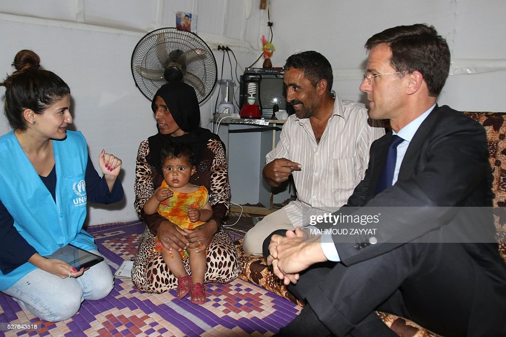 Dutch Prime Minister Mark Rutte (R) speaks to a Syrian family during a visit to a Syrian refugee camp, in the southern Lebanese town of Zahrani on May 3, 2016. / AFP / MAHMOUD