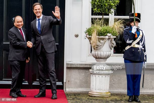 Dutch Prime Minister Mark Rutte waves as he welcomes his Vietnamese counterpart Nguyen Xuan Phuc for a work dinner at the Catshuis in The Hague on...