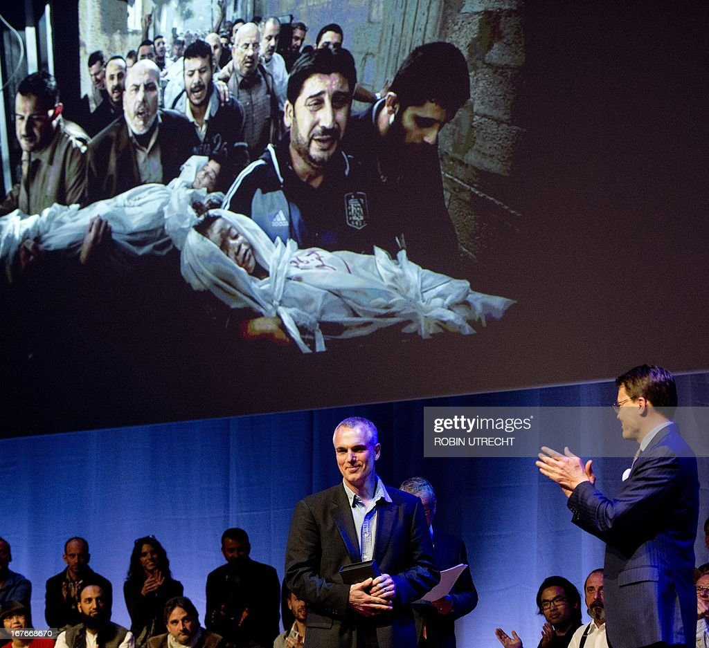 Dutch Prince Constantijn (R) applauds Swedish photographer and World Press Photo of the Year winner Paul Hansen (L) on stage in front of his winning picture during the World Press Photo Award of 2012 in Amsterdam, The Netherlands on April 27, 2013. The image shows men carrying the bodies of two Palestinian children who were killed in an Israeli missile strike.