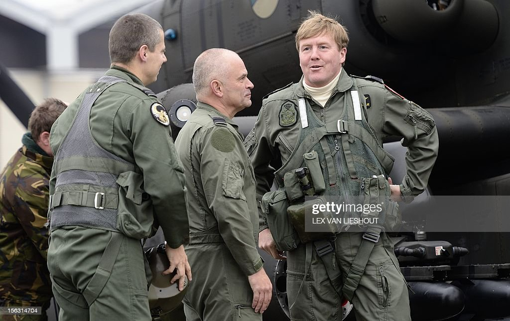Dutch Prince Willem-Alexander (R) talks with soldiers during a visit to the Defence Helicopter Command (DHC) at Gilze Rijen airbase on November 13, 2012. The Prince paid a visit to the airbase to get informed about the cooperation between air and ground crews. netherlands out