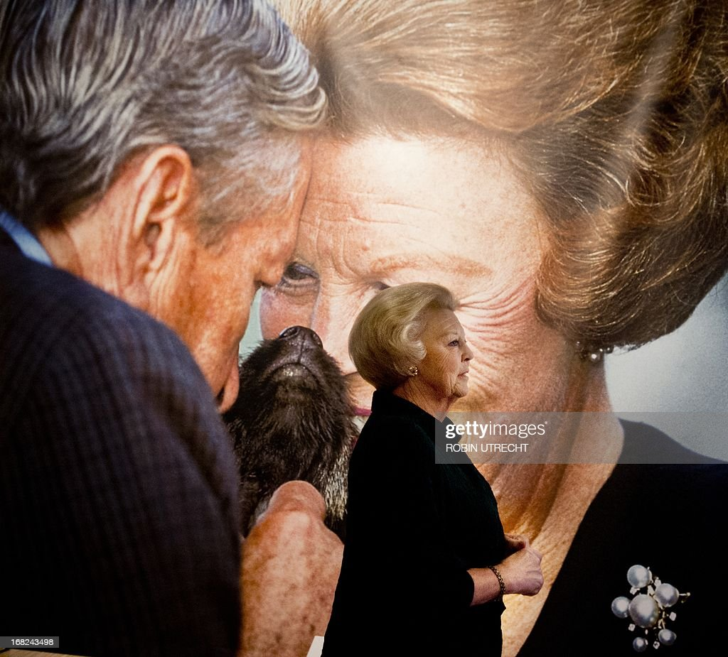 Dutch Princess Beatrix looks at pictures of herself at the exhibition 'Onze Koningin' (Our Queen) at the Beurs van Berlage in Amsterdam on May 7, 2013. The exhibition includes 145 photos of Beatrix as Queen and Princess, all made by Dutch press agency ANP. The exhibition is open untill May 26.