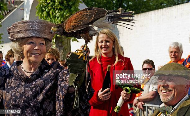 Dutch Queen Beatrix holds a Harris Hawk which belongs to Dutch falconer Rob van Dipten as Princess Mabel looks on during the Queen's day celebration...