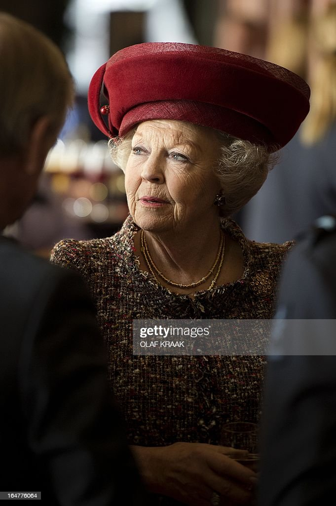 Dutch Queen Beatrix speaks to veterans during her visit to the Dutch Defence Academy in Breda, The Netherlands, on March 27, 2013. The Queen added a cravatte with the words 'Kosovo 1999' on the flag of the Royal Air Force during her visit to the academy. AFP PHOTO/ OLAF KRAAK / POOL