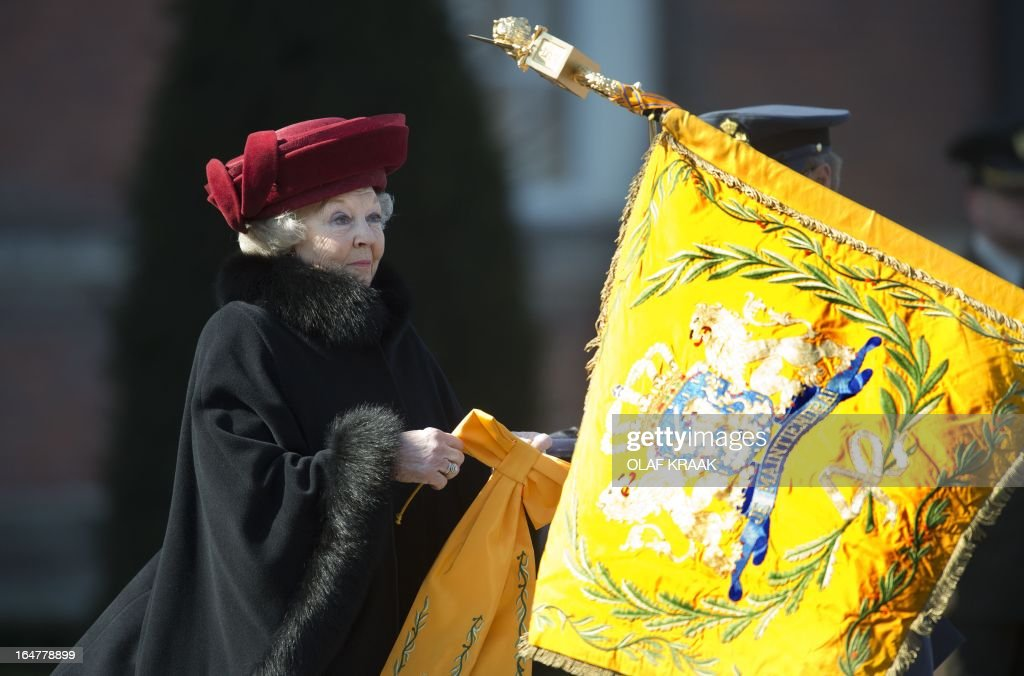 Dutch Queen Beatrix ties a ribbon, with the words 'Kosovo 1999', to the Air Force flag during her visit to the Dutch Defence Academy in Breda, The Netherlands, on March 27, 2013. The Queen expressed her appreciation for the work of the Royal Air Force during Operation Allied Force over Serbia and Kosovo in 1999. AFP PHOTO/ OLAF KRAAK netherlands out