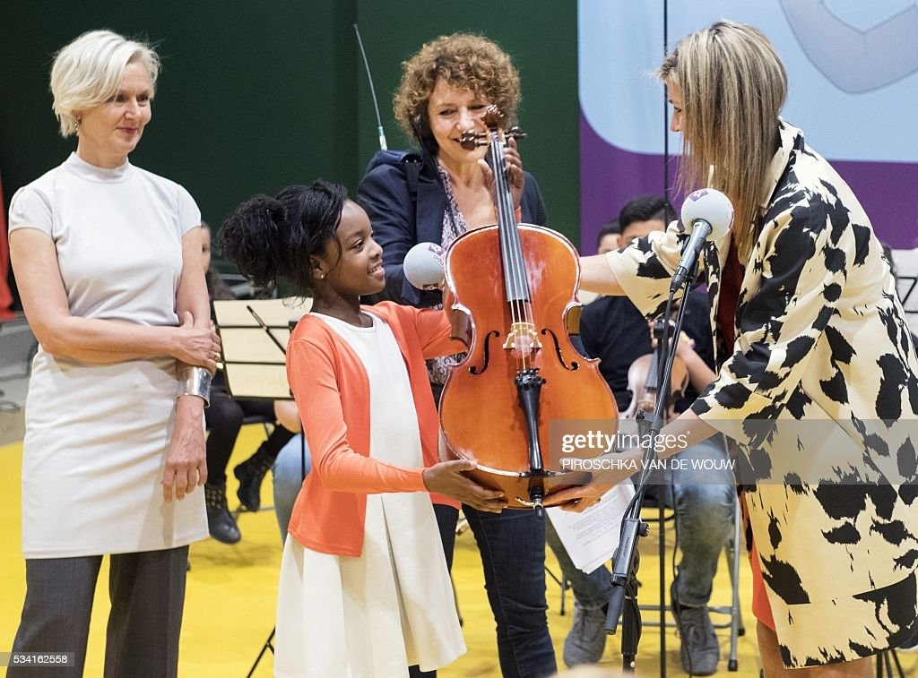 Dutch Queen Maxima gives a violoncello to a child during a fundraising of music instruments for children for the start of NPO Radio 4 Classic in Den Bosch, The Netherlands on May 25, 2016. / AFP / ANP / Piroschka van de Wouw / Netherlands OUT