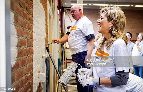 Dutch Queen Maxima laughs as she paints a wall in the sports area of a cultural centre in the village Tricht on March 21 2015 Members of the Dutch...