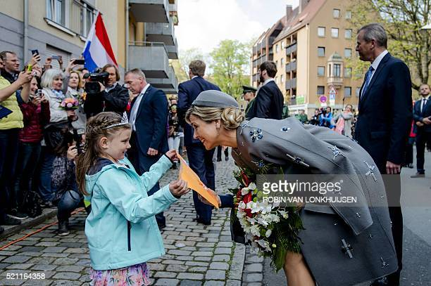 Dutch Queen Maxima receives a drawing by a girl as she visits the Siemens Healthcare complex in Erlangen on April 14 as part of a twoday visit of the...