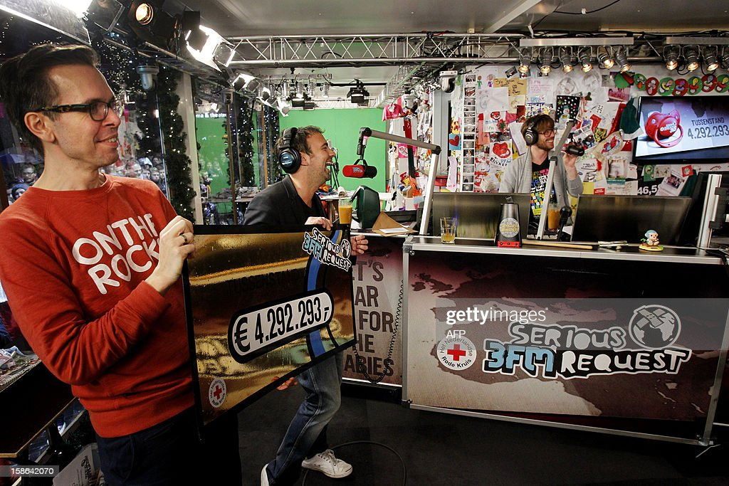 Dutch radio DJ's Michiel Veenstra (L) and Gerard Ekdom (R) show the amount of money (4.292.293 euros) they already raised, five days after the start of Serious Request, in Enschede, the Netherlands, on December 22, 2012. Serious Request is an annual project by Dutch radio station 3FM in which they collect money for projects of the Red Cross. During the project, three DJs live in a house of glass for six days without eating anything, only drinking a special juice to stay fit. The charity event started on December 18 and ends on December 24. AFP PHOTO / ANP / ADE JOHNSON