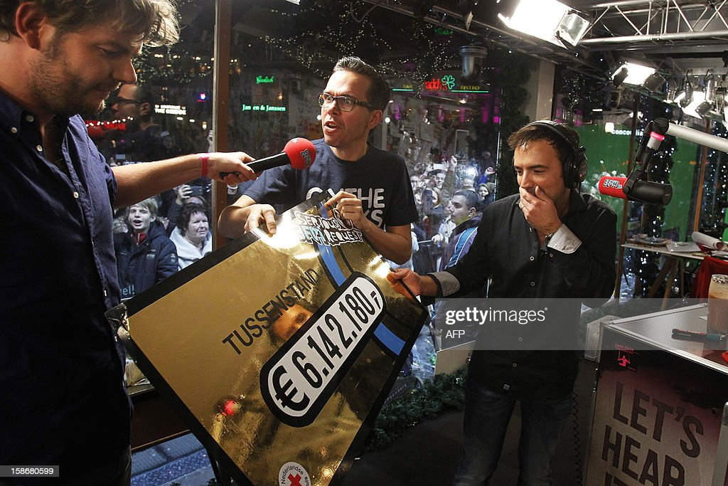 Dutch radio DJ's Michiel Veenstra (C) and Gerard Ekdom (R) show the amount of money (6.142.180 euros) they already raised, six days after the start of the 'Serious Request' fundraising initiative, in Enschede, the Netherlands, on December 23, 2012. Serious Request is an annual project by Dutch radio station 3FM in which they collect money for projects of the Red Cross. During the project, three DJs live in a house of glass for six days without eating anything, only drinking a special juice to stay fit. The charity event started on December 18 and ends on December 24. AFP PHOTO / ANP / ADE JOHNSON