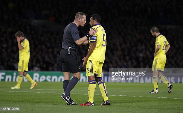 Dutch referee Danny Makkelie talks to Maribors Brazilian striker Marcos Tavares after he awards a penalty to Chelsea during the UEFA Champions League...