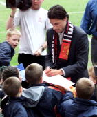 Dutch soccer player Ruud Van Nistelrooy wearing a Manchester United scarf signs autographs for fans at Old Trafford in Manchester 27 April 2001 Van...
