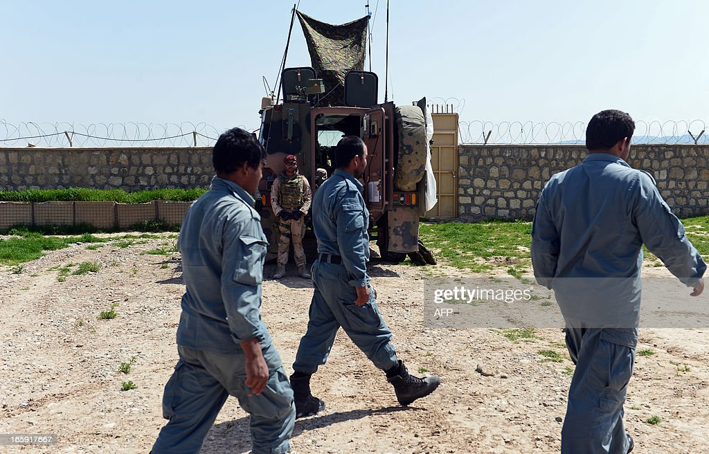 A Dutch soldier (2nd L) looks on as Afghanistan policemen walk past at a police training centre in Ali Abad district in Kunduz province on April 7, 2013. The Dutch have 500 soldiers which are part of International Security Assistance Force (ISAF) in Afghanistan. AFP PHOTO / Massoud HOSSAINI