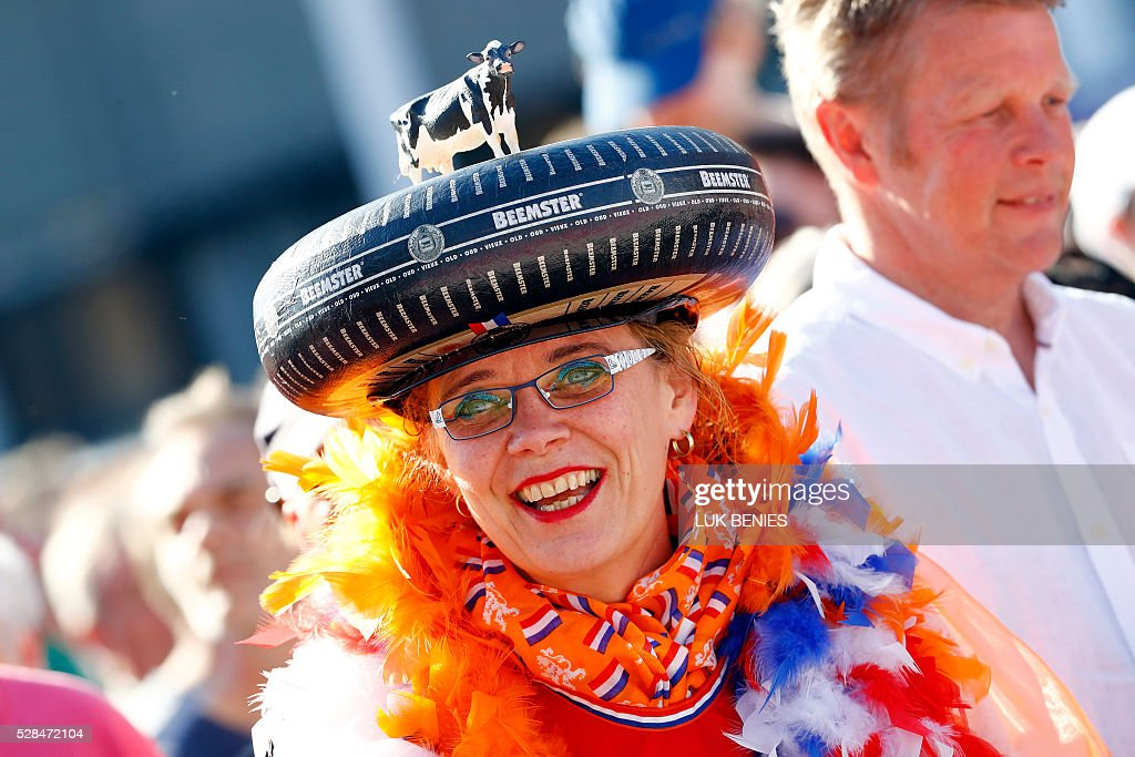 A dutch supporter wears a Beemster hat in the shape of a tire with a cow on its top during the team presentation for the 99th Giro d'Italia (Tour of Italy) on May 5, 2016 in Apeldoorn. / AFP / LUK