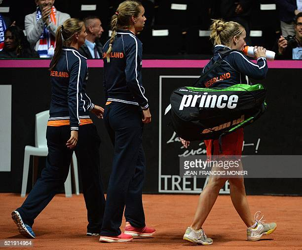 Dutch tennis players Cindy Burger Arantxa Rus and Richel Hogenkamp leave the court after they lost the Fed Cup semifinal against France in Trelaze...