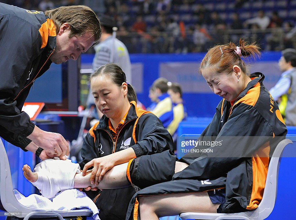 A Dutch trainer (L) and player Li Jiao (C) attend to the injured foot of teammate <a gi-track='captionPersonalityLinkClicked' href=/galleries/search?phrase=Li+Jie+-+Table+Tennis+Player&family=editorial&specificpeople=12783702 ng-click='$event.stopPropagation()'>Li Jie</a> (R) during the latter's quarter-final match against Singapore at the World Team Table Tennis Championships in Guangzhou, in China's Guangdong province on February 28, 2008. Singapore were leading their quarter-final clash with the Netherlands 2-0 when <a gi-track='captionPersonalityLinkClicked' href=/galleries/search?phrase=Li+Jie+-+Table+Tennis+Player&family=editorial&specificpeople=12783702 ng-click='$event.stopPropagation()'>Li Jie</a> twisted her ankle in the opening game of the crucial third match, forcing the Europeans to abandon the encounter.