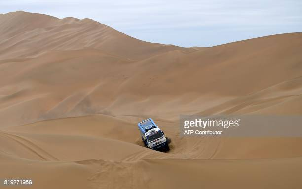 Dutch truck driver Gerard De Rooy and codrivers Darek Rodewald of Poland and Moises Torrallardona of Spain ride over sand dunes as they compete...