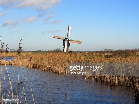 Dutch windmill along canal : Stock Photo