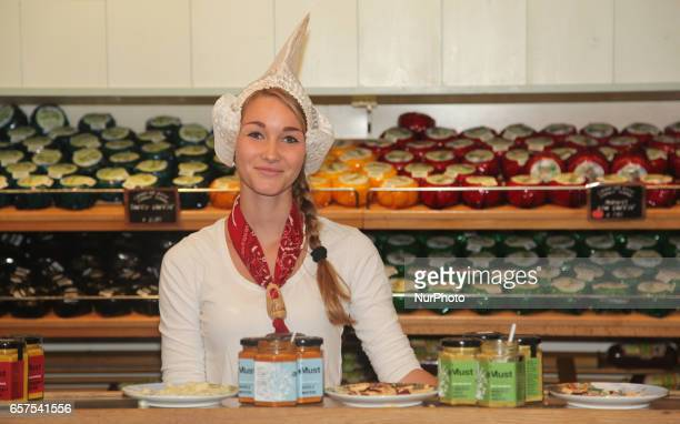 Dutch woman selling cheese at a small shop in the town of Zaanse Schans Holland Netherlands Europe