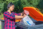 European woman throwing plastic garbage in container. The dutch woman with black hair is dropping the trash in the trash bin. In the netherlands the container for plastic has a grey color with an oran