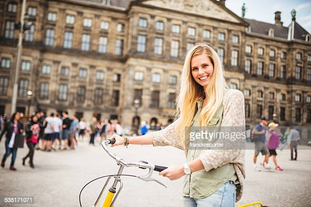 Dutch woman with bicycle in amsterdam dam square